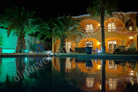 VIlla at night with pool and palm trees